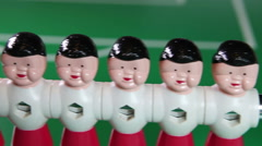 Toy football players stand in a row, and three have fallen and lie Stock Footage
