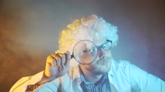 Funny scientist, like Einstein with a magnifying glass Stock Footage