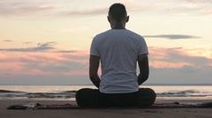 Young man sitting on the beach and meditating Stock Footage