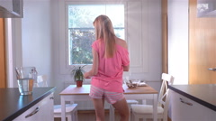 A slender happy woman in pajama preparing corn flakes with milk and dancing. Stock Footage