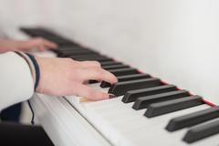 Women's hands on the keyboard of the piano Stock Photos