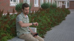 Casual dressed man sit on the bench and use his smart watch and smartphone Stock Footage
