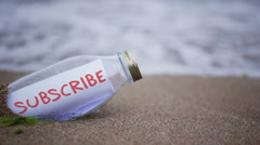 Subscribe written on a message washed ashore Stock Footage