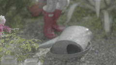 Kids' Red Rainboots dodge water from a hose Stock Footage