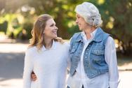 Two pretty women smiling and walking on the street Stock Photos