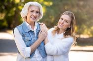 Two pretty smiling women standing in the park Stock Photos