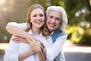 Two smiling friendly woman hugging in the park Stock Photos