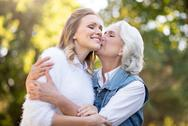 Beautiful gray haired woman kissing her daughter in the cheek Stock Photos