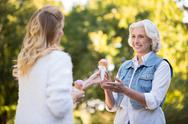 Young blonde woman giving an icecream to her mother Stock Photos