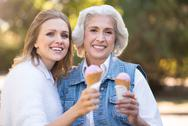 Charming women with an ice cream walking in the park Stock Photos