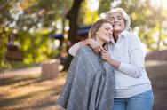Two delighted women hugging and smiling in the park Stock Photos