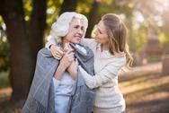 Pretty smiling woman caring about her mother Stock Photos