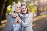 Two cheerful beautiful women smiling and hugging Stock Photos