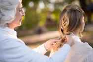 Gray haired women plaiting her daughter hair Stock Photos