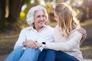 Two happy smiling women sitting on the ground and talking Stock Photos