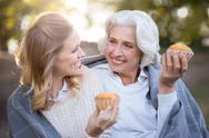 Smiling emotional women sitting on the ground and holding cakes Stock Photos