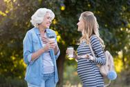 Two pretty smiling women drinking coffee in the park Stock Photos