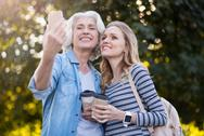 Two smiling happy women taking a picture Stock Photos