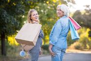 Two happy delighted women holdingpackets and walking in the park Stock Photos