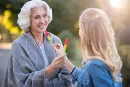 Two happy smiling women showing each other lollypops Stock Photos