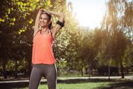 Cheerful girl preparing for morning training in the park Stock Photos