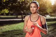 Concentrated girl holding the bottle of water after training Stock Photos