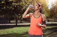 Delighted girl drinking water after morning exercises Stock Photos
