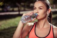 Tired girl drinking water after hard training Stock Photos