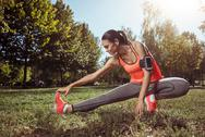 Young girl doing her morning stretching in the park Stock Photos