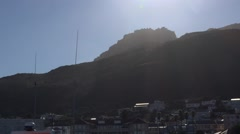 Cape Town mountain sun flare and Kalk Bay fishing boat Stock Footage