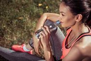 Beautiful girl drinking water after training outdoors Stock Photos