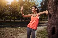 Smiling girl waving to someone in the park after training Stock Photos