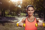 Delighted girl holding dumbbells on her outdoors training Stock Photos