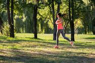Athletic girl running in the park Stock Photos
