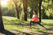 Smiling girl making lunges in the park Stock Photos