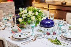Beautifully decorated table set with flowers, candles, plates and serviettes for Stock Photos