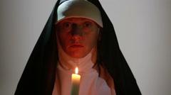 Woman nun praying at night. burning candles. Woman in clothes nuns Stock Footage