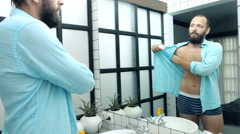 Young man applying antiperspirant on his armpit in bathroom  Stock Footage