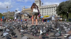 Girl jumping amongst pigeons Stock Footage