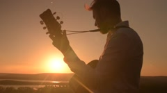 Young attractive man playing guitar outdoors Stock Footage