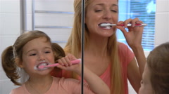 Young attractive mom and her cute daughter brush their teeth. Stock Footage