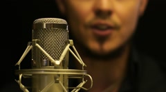 Young attractive man singing behind microphone Stock Footage