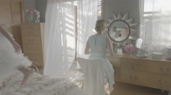 Two little girls play on a bed as their mother sits at a nearby mirror (MRT) Stock Footage