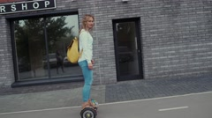 Young woman Using Gyroscooter Platform. Bright yellow backpack Stock Footage