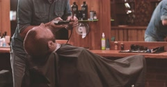 Barber cutting beard with clipper at barbershop 4k video. Styling client beard Stock Footage