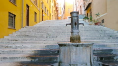 Street fountain in a European city on the street. People quench thirst drinking Stock Footage