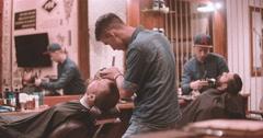 Hairdressing at vintage barbershop 4k video. Barbers working with lumberjack Stock Footage