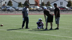 The coach carries injured player off the field at this youth football game 3709 Stock Footage