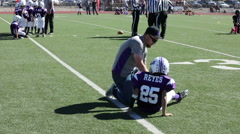 The coach helps injured player off the field at this youth football game, 3710 Stock Footage