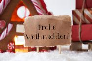 Gingerbread House With Sled, Frohe Weihnachten Means Merry Christmas Stock Photos